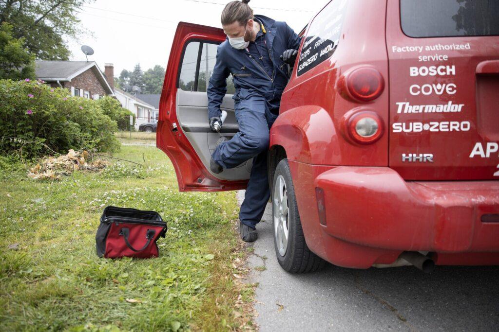 Craig Maloney, an appliance technician for Metropolitan Services, disinfects his boots and clothing after repairing a refrigerator in South Portland last Wednesday. Businesses in Maine that rely on in-home service are either finding ways to adapt to the coronavirus pandemic or staying on the sidelines.