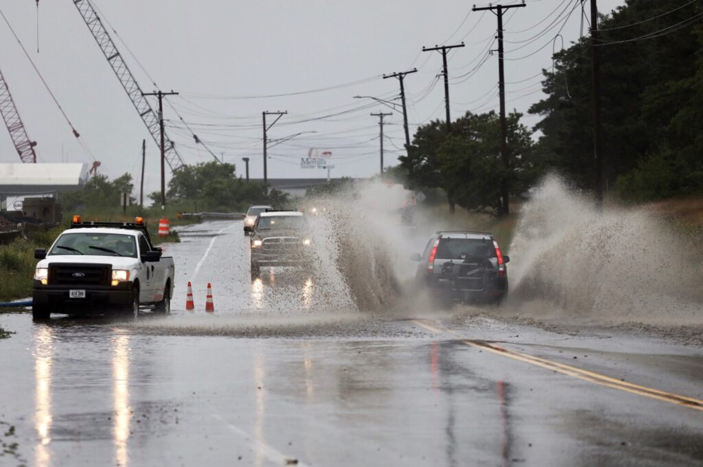 A vehicle plows through a flooded section of Commercial Street in Portland on Monday.