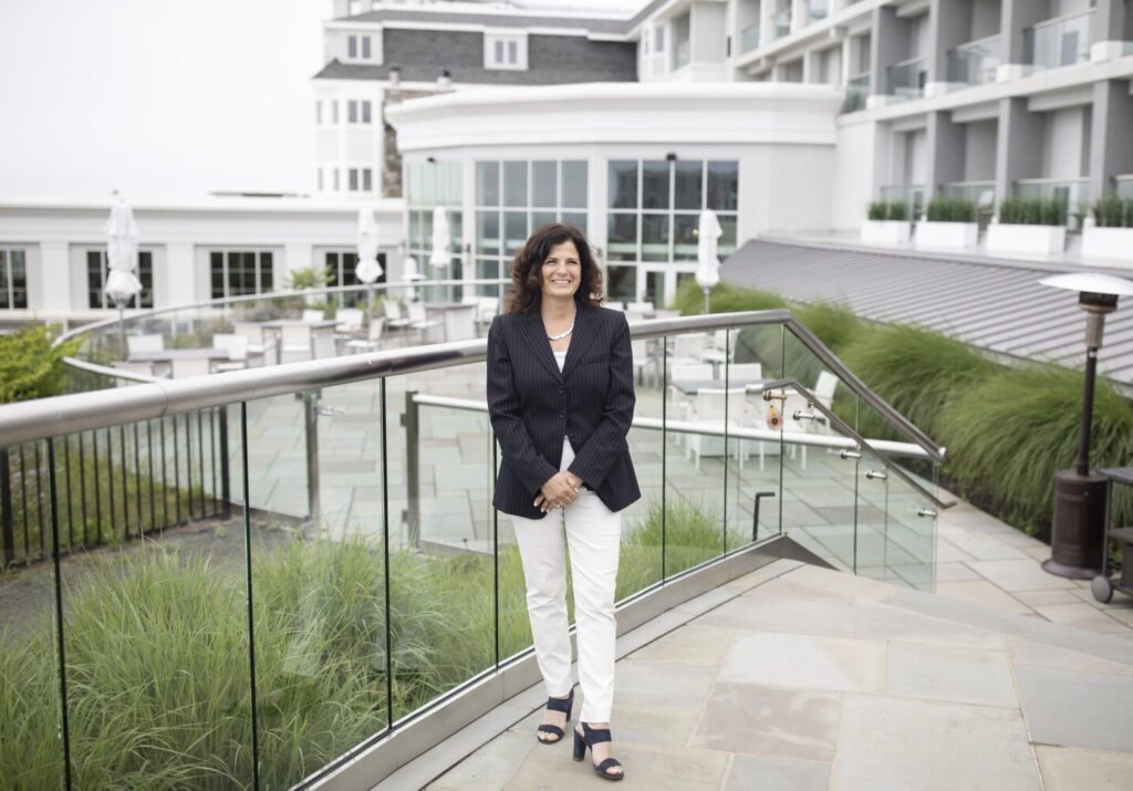 Nancy White, managing director of Cliff House Maine in York, poses on the back terrace of the hotel Tuesday. Cliff House Maine expects to fill about half of its 226 rooms over the Fourth of July weekend, said White. A year ago, nearly every room was booked.
