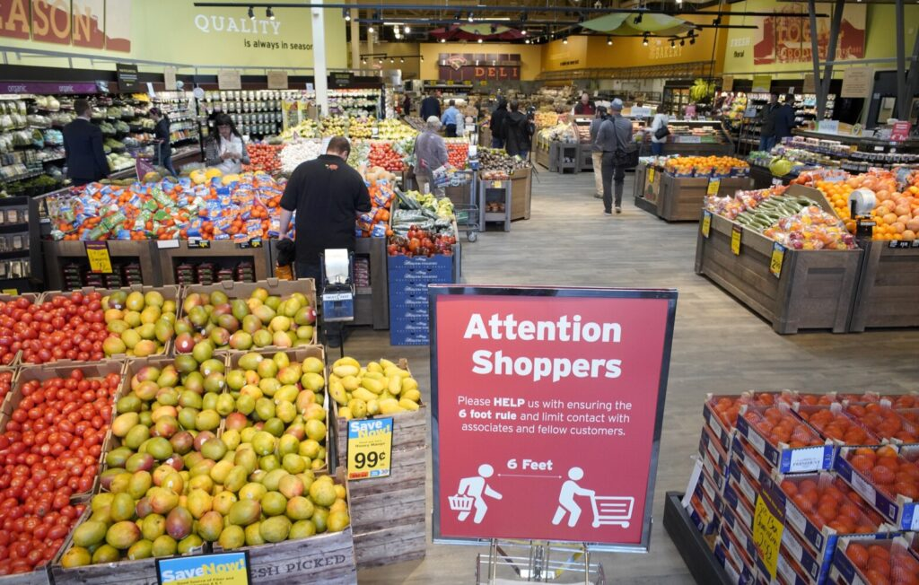 A sign at the entrance to the Hannaford supermarket in Scarborough on March 27, reminds customers to stay six feet apart while shopping in the store. Grocers in Maine and across the U.S. are rebuilding their supply chains after the pandemic disrupted their businesses, first with customers buying up excess supply, followed by viral outbreaks and government-imposed restrictions.