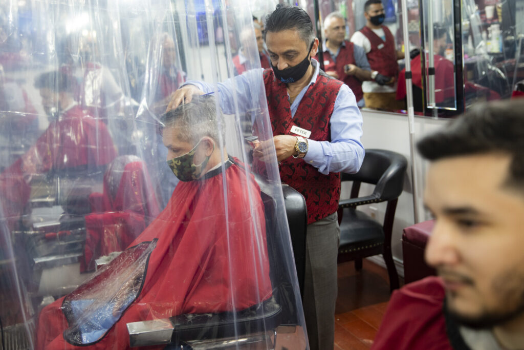 Peter Shamuelov, center, wears a protective mask as he gives a haircut to a customer at Ace of Cuts barbershop on Monday in New York. For the first time in three months, New Yorkers are able to dine out, browse the city's destination stores and get haircuts.