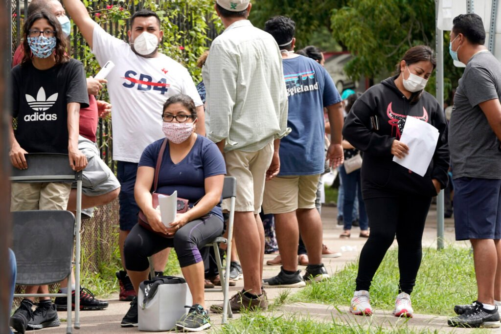 People wait in line at a free COVID-19 testing site provided by United Memorial Medical Center at the Mexican Consulate on Sunday in Houston. Confirmed cases of the coronavirus in Texas continue to surge. Texas Gov. Greg Abbott, on Friday, shut down bars again and scaled back restaurant dining as cases climbed to record levels after the state embarked on one of America's fastest reopenings.