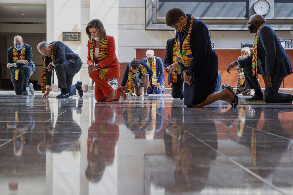 House Speaker Nancy Pelosi of California, center, and other members of Congress kneel and observe a moment of silence at the Capitol's Emancipation Hall on Monday on Capitol Hill in Washington, reading the names of George Floyd and others killed during police interactions. Democrats proposed a sweeping overhaul of police oversight and procedures Monday.