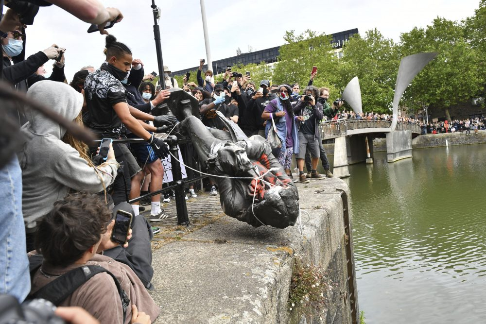 Protesters throw a statue of slave trader Edward Colston into Bristol Harbour, during a Black Lives Matter rally, in Bristol, England, on Sunday, in response to the killing of George Floyd by police officers in Minneapolis.