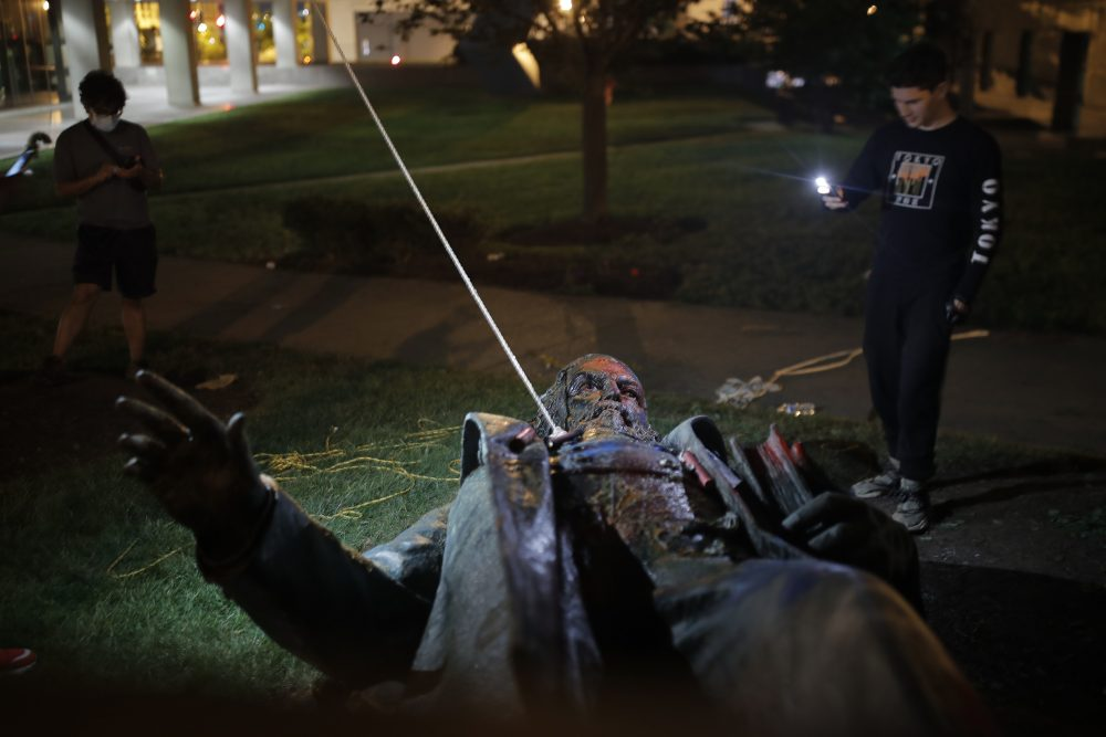 People film the only statue of a Confederate general, Albert Pike, in the nation's capital after it was toppled by protesters and set on fire in Washington early Saturday morning.