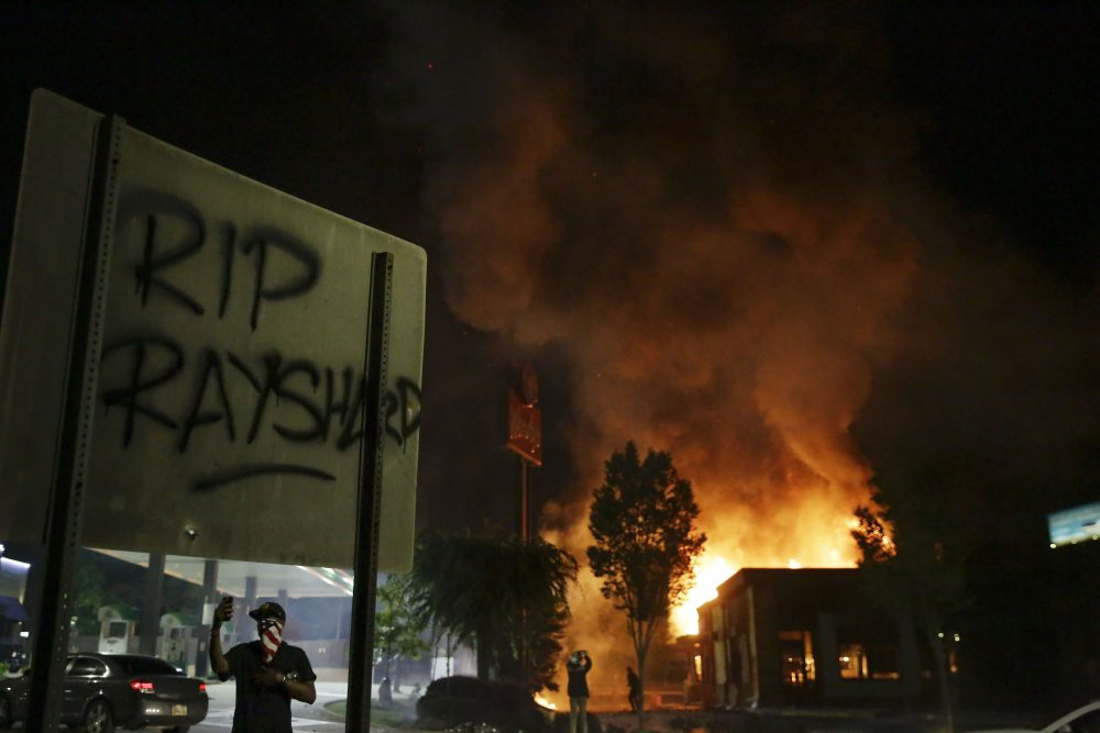 """""""RIP Rayshard"""" is spray painted on a sign as as flames engulf a Wendy's restaurant during protests Saturday in Atlanta. The restaurant was where Rayshard Brooks was shot and killed by police Friday evening following a struggle in the restaurant's drive-thru line."""