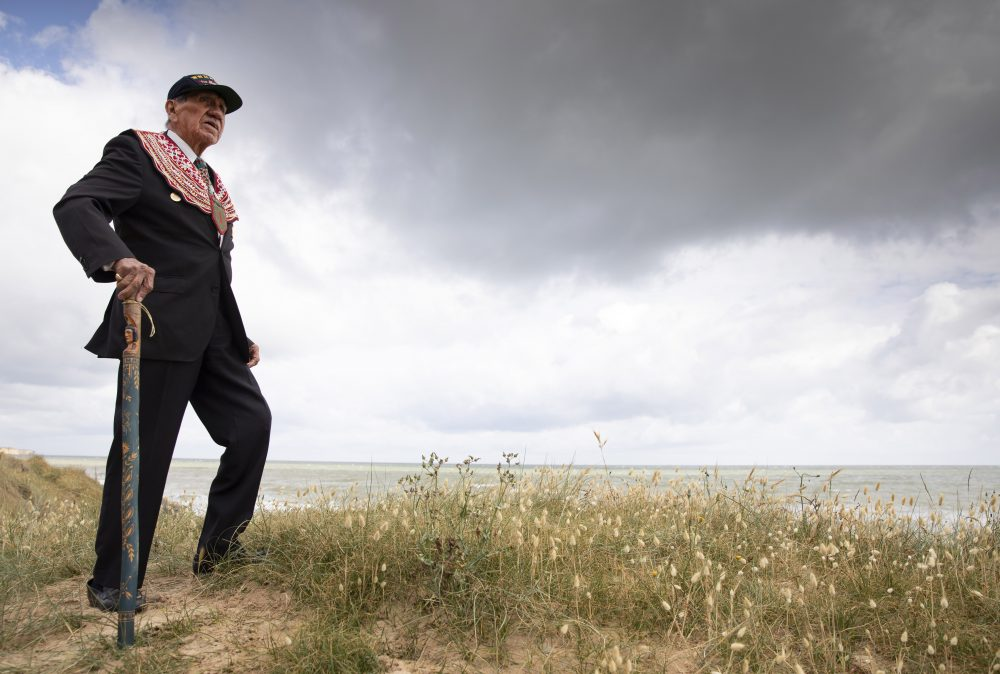 World War II D-Day veteran and Penobscot Elder from Maine, Charles Norman Shay poses on the dune overlooking Omaha Beach prior to a ceremony at his memorial on Friday.
