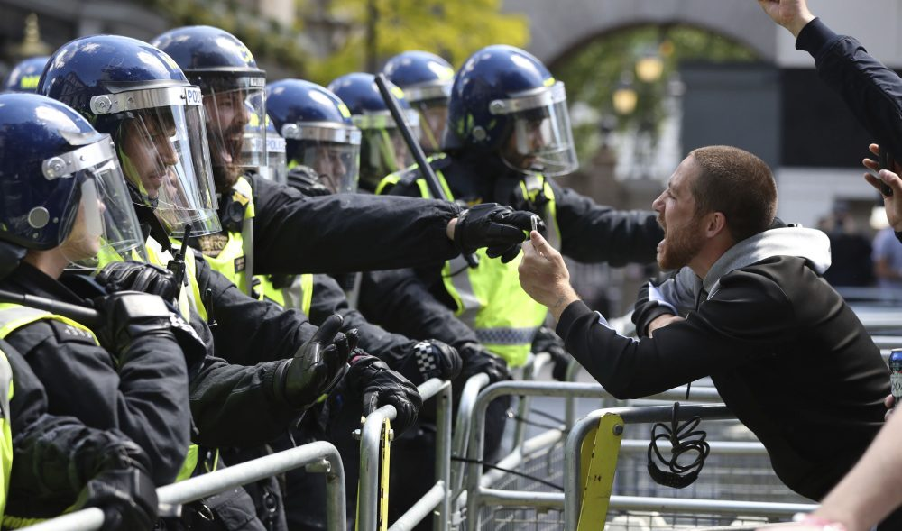 Police are confronted by a protester Saturday in Whitehall near Parliament Square, London, during a protest by the Democratic Football Lads Alliance against a Black Lives Matter protest. The death of George Floyd in the United States has prompted demonstrations by far-right groups as well as the Black Lives Matter movement and provoked a wider debate regarding many historical figures and Britain's colonial past.