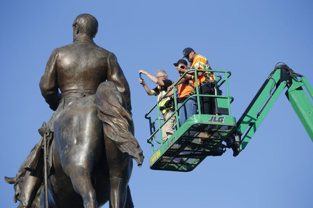 An inspection crew from the Virginia Department of General Services inspects the statue of Confederate Gen. Robert E. Lee on Monday in Richmond, Va. Gov. Ralph Northam has ordered the removal of the statue.