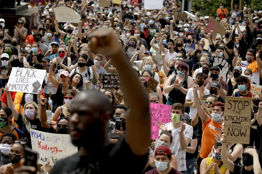 People hold signs as they listen to a speaker in front of city hall in downtown Kansas City, Mo., on Friday, June 5, 2020, during a rally to protest the death of George Floyd.