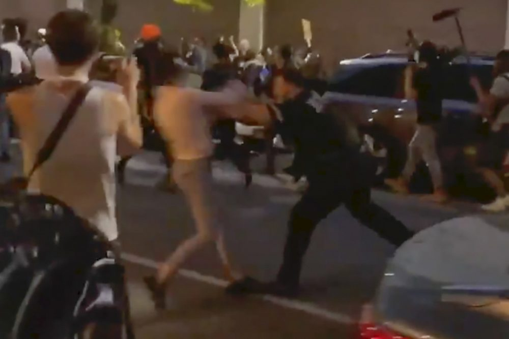 In this photo taken from video, New York police officer Vincent D'Andraia pushes Dounya Zayer during a protest in Brooklyn on May 29. D'Andraia, who was caught on video shoving Zayer to the ground, was charged Tuesday with assault and other crimes in the confrontation.