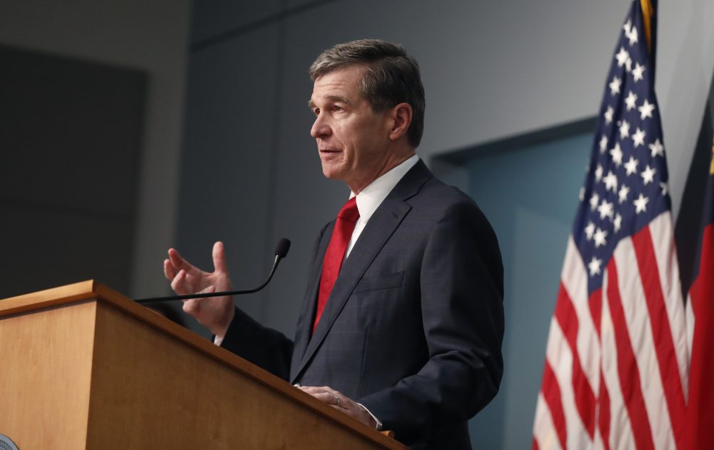 "North Carolina Gov. Roy Cooper speaks during a briefing at the Emergency Operations Center in Raleigh, N.C., on Tuesday. President Trump announced the news via tweet, complaining that Cooper and other officials ""refuse to guarantee that we can have use of the Spectrum Arena"" and were not ""allowing us to occupy the arena as originally anticipated and promised."""