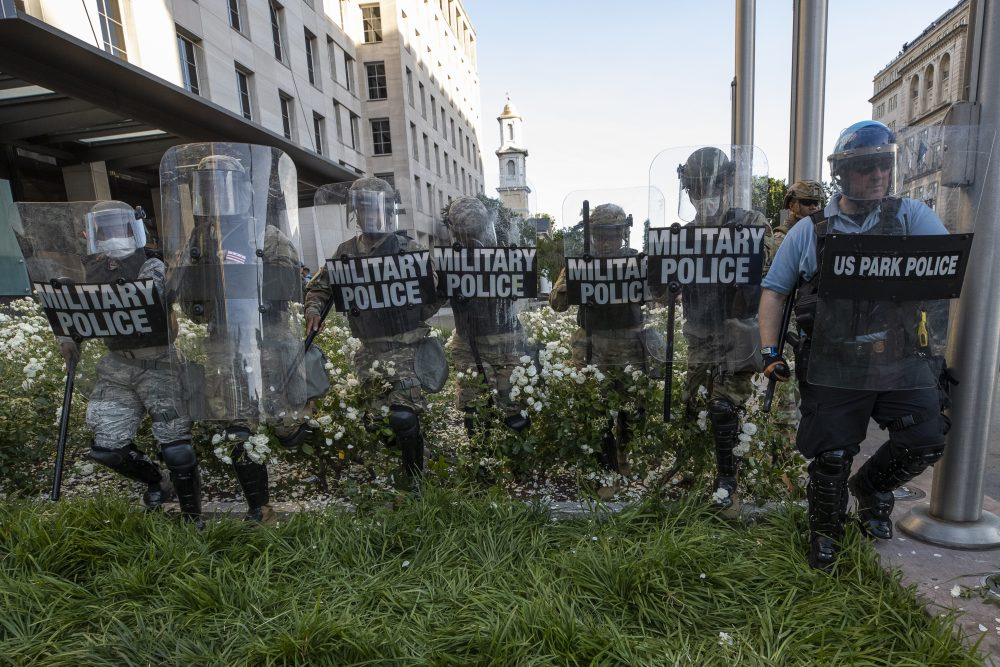 District of Columbia National Guard, and U.S. Park Police, advance through the white roses in front of the AFL-CIO headquarters as they move demonstrators back in Washington.