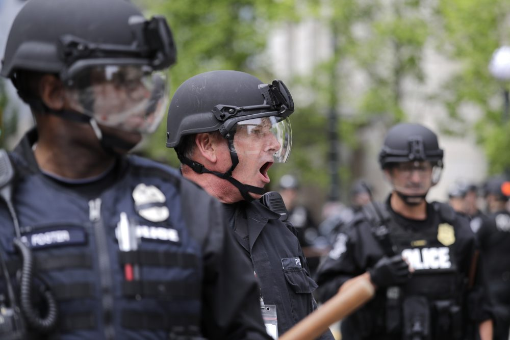 A Seattle police officer yells out orders at Seattle City Hall as protesters march toward them Wednesday, June 3, 2020, protesting the death of George Floyd in Minneapolis.