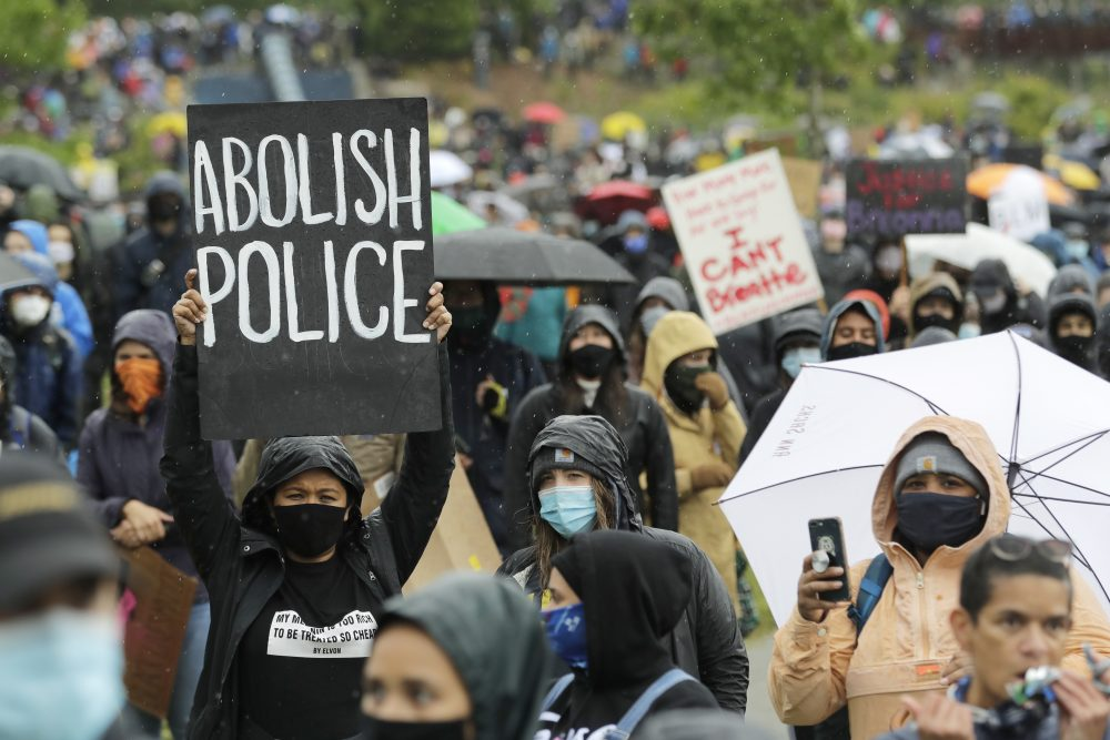 """A protester holds a sign Friday during a """"Silent March"""" against racial inequality and police brutality that was organized by Black Lives Matter Seattle-King County. A federal judge ordered Seattle police Friday to temporarily stop using tear gas, pepper spray and flash-bang devices to break up largely peaceful protests."""