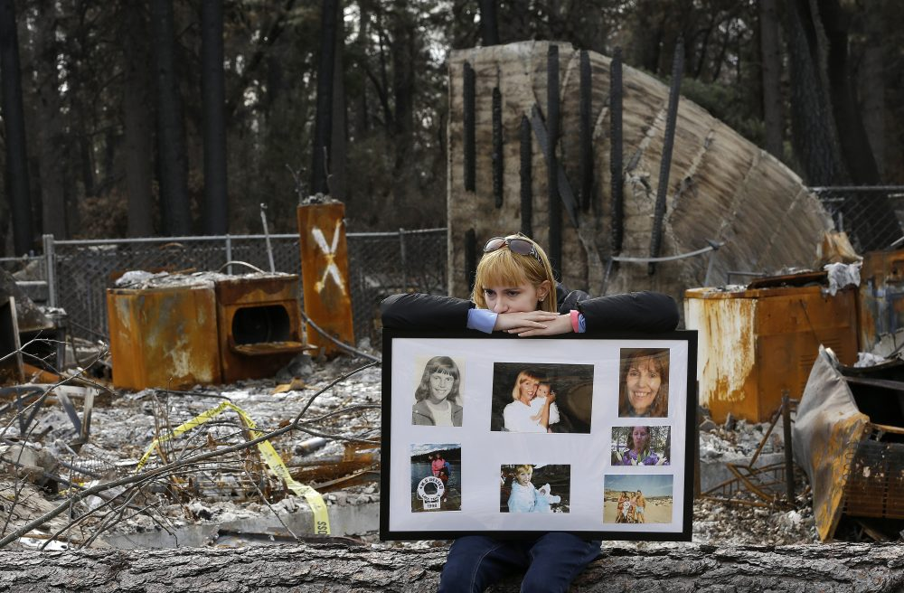 Christina Taft, the daughter of Camp Fire victim Victoria Taft, displays a collage of photos of her mother, at the burned out ruins of the Paradise, Calif., home where she died in 2018. Pacific Gas & Electric plead guilty for the deadly wildfire that nearly wiped out the Northern California town of Paradise in 2018.