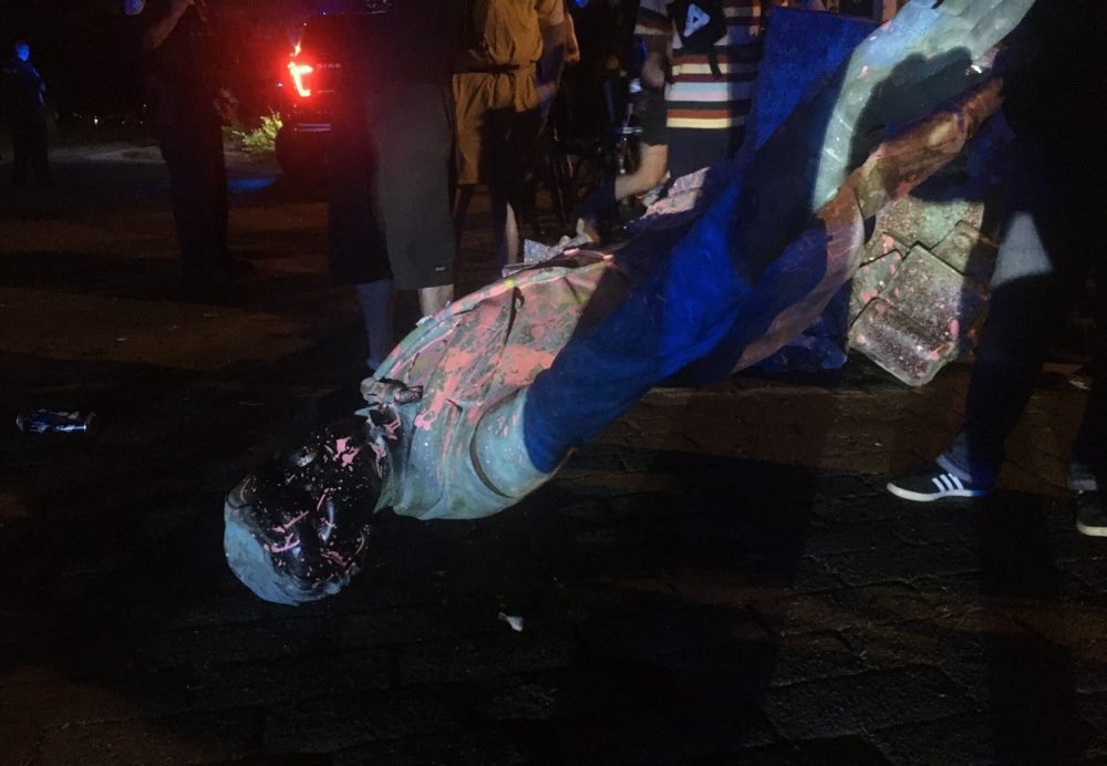 The statue of Confederate President Jefferson Davis is splattered with paint after being toppled Wednesday night in Richmond, Va.