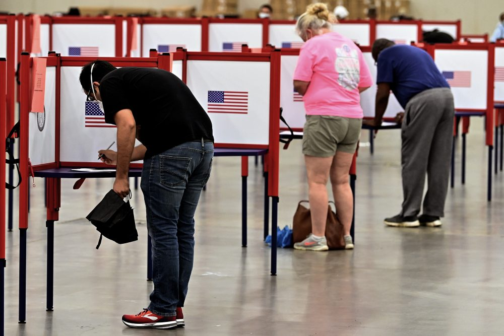 Voters fill out their ballots at the Kentucky Exposition Center in Louisville, Ky., on Tuesday. In an attempt to prevent the spread of the coronavirus, neighborhood precincts were closed and voters that didn't cast mail in ballots were directed to one central polling location.
