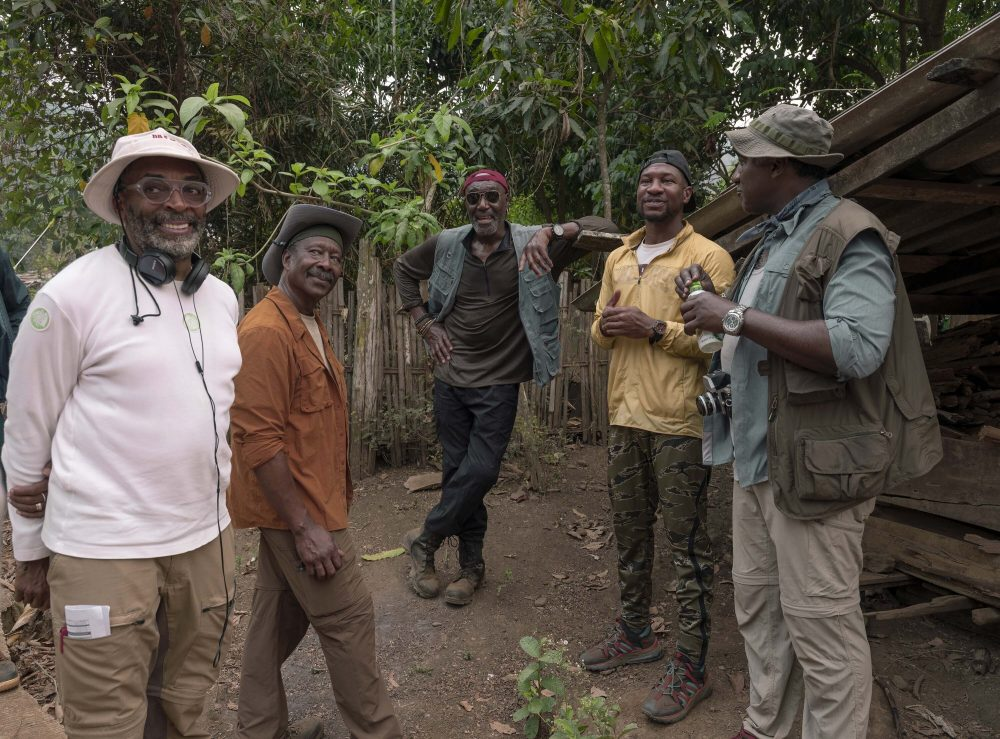 """This image released by Netflix shows, from left, filmmaker Spike Lee, from left, with Clarke Peters, Delroy Lindo, Jonathan Majors and Norm Lewis on the set of """"Da 5 Bloods."""""""