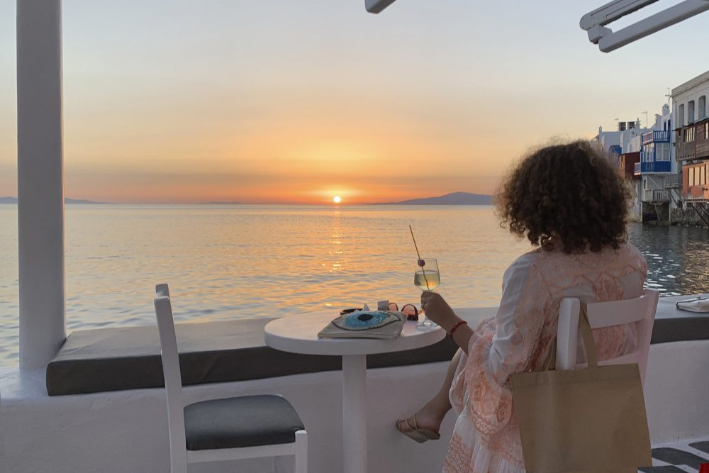 A visitor watches the sunset at a bar in Mykonos, Greece, on June 9. Greece will officially launch its tourism season Monday after keeping the country's infection rate low.