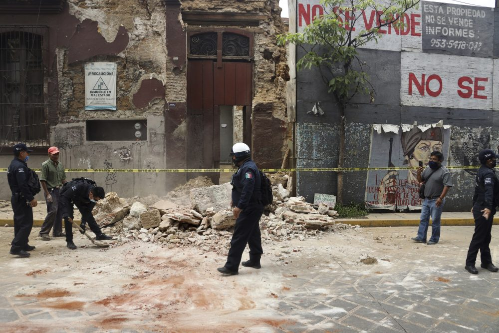 A policeman removes rubble from a building damaged by an earthquake in Oaxaca, Mexico, on Tuesday.