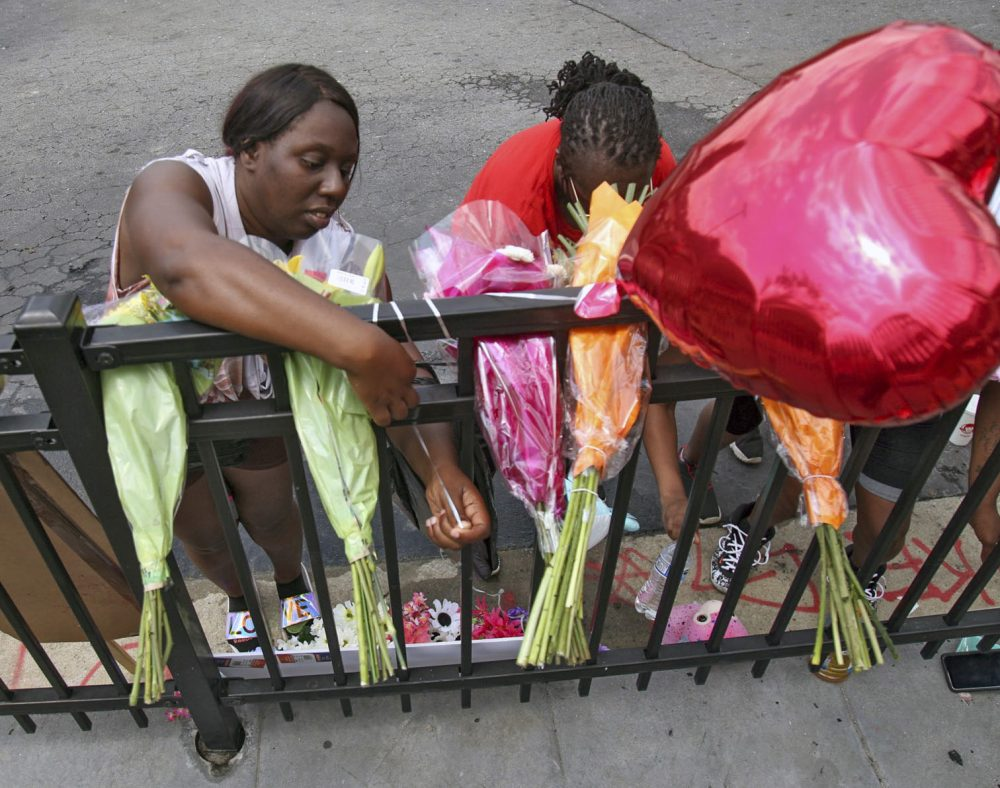 People attend to a memorial at the site of a Wendy's restaurant Sunday in Atlanta. On Saturday, protesters set fire to the Wendy's where Rayshard Brooks, a black man, was shot and killed by Atlanta police Friday evening following a struggle in the drive-thru line. Steve Schaefer/Atlanta Journal-Constitution via AP