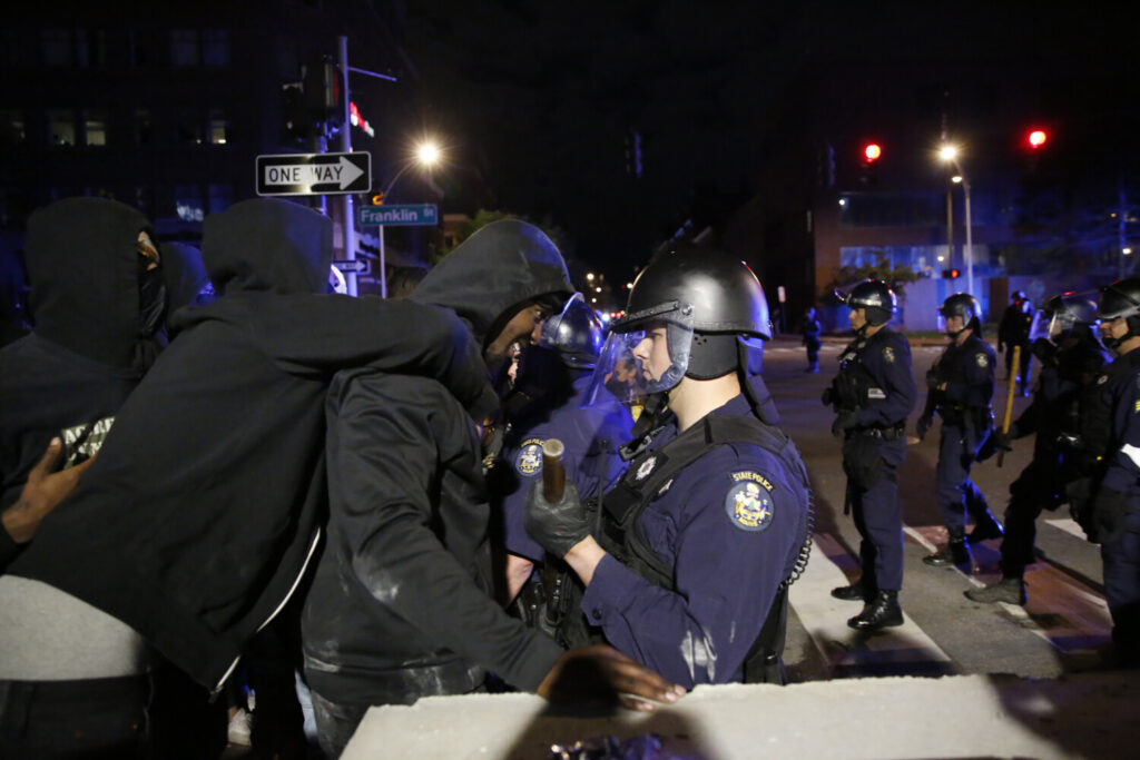 Police clash with protesters at the intersection of Franklin and Middle Streets.