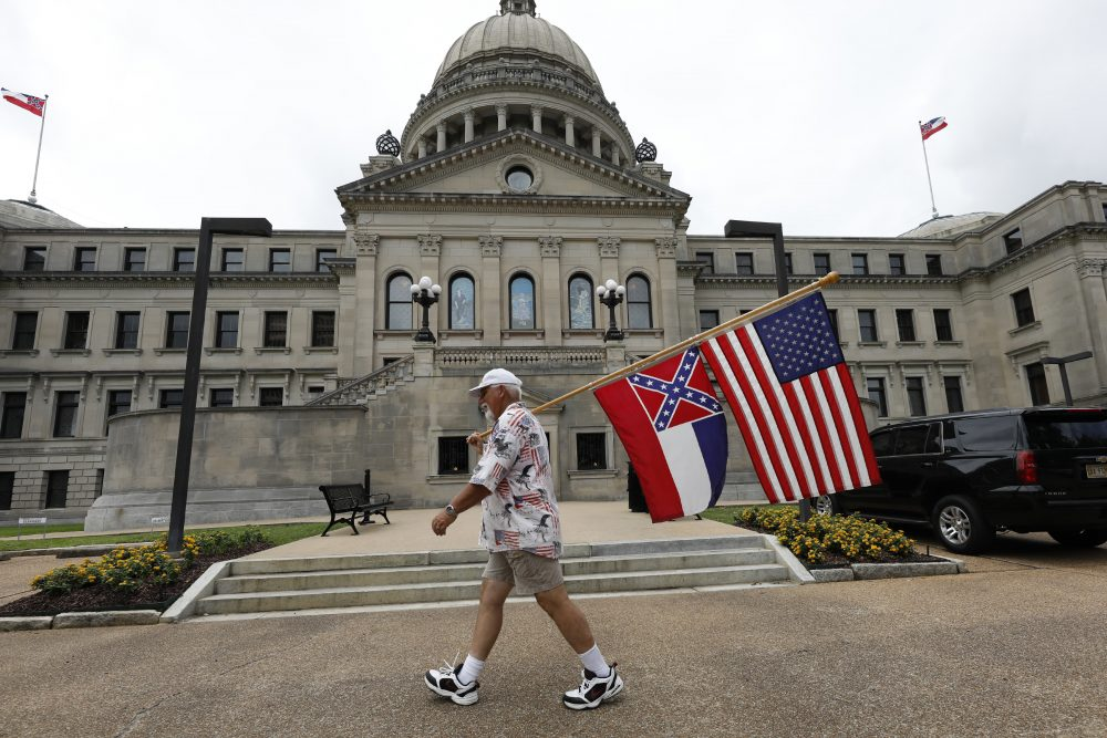 Don Hartness of Ellisville, walks around the Capitol carrying the current Mississippi state flag and the American flag on Saturday in Jackson, Miss.
