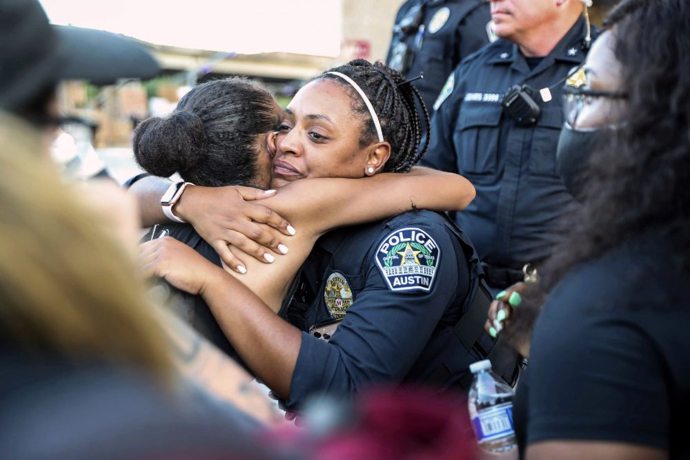 Police officer Alexandra Parker hugs a protester June 4 at the Austin Police Department headquarters during a Black Lives Matter rally in Austin.