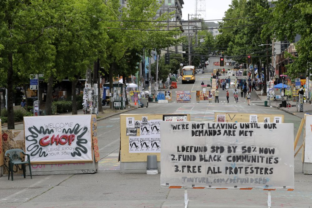 A sign on the street welcomes visitors and a list of demands is posted Wednesday, inside the CHOP (Capitol Hill Occupied Protest) zone in Seattle. (AP Photo/Ted S. Warren)