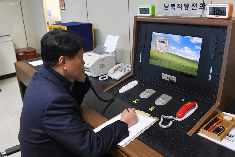 FILE - In this Jan. 3, 2018 file photo, a South Korean government official communicates with a North Korean officer during a phone call on the dedicated communications hotline  in Paju, South Korea, in 2018. North Korea said Tuesday it'll cut off all communication channels with South Korea as it escalates its pressure on the South for failing to stop activists from floating anti-Pyongyang leaflets across the border.