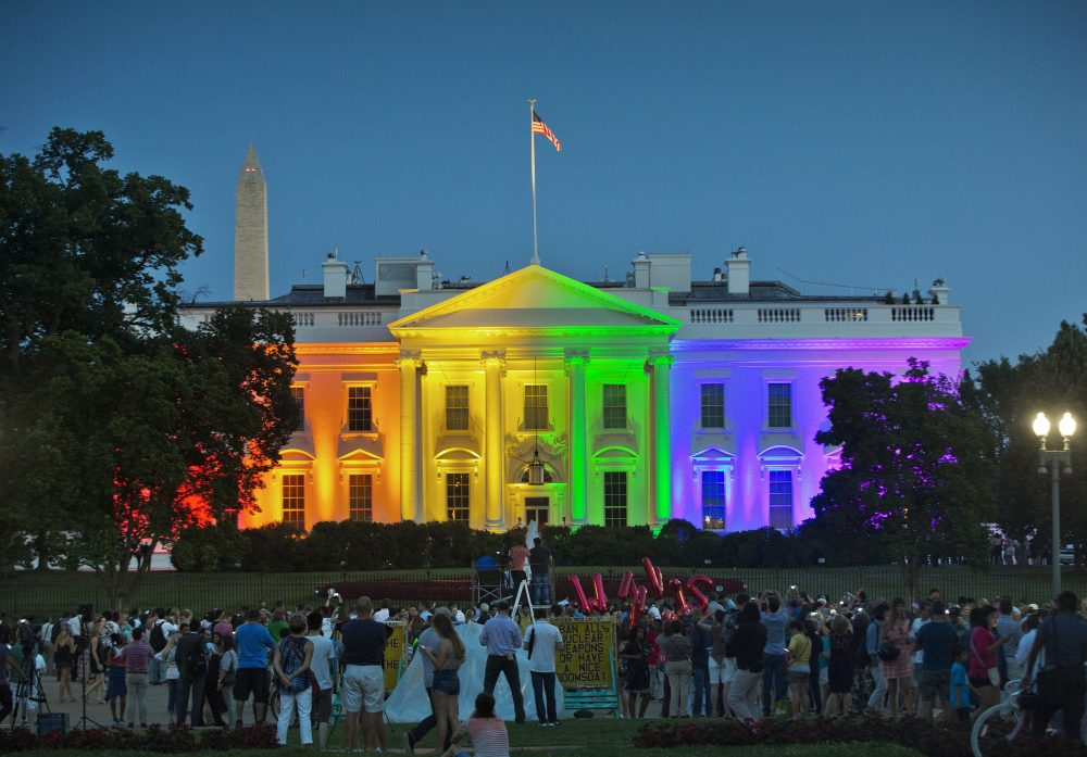 People gather in Lafayette Park on June 26, 2015, to see the White House illuminated with rainbow colors in commemoration of the Supreme Court's ruling to legalize same-sex marriage. On Friday, the Trump administration finalized a regulation that overturns Obama-era protections for transgender people against sex discrimination in health care.