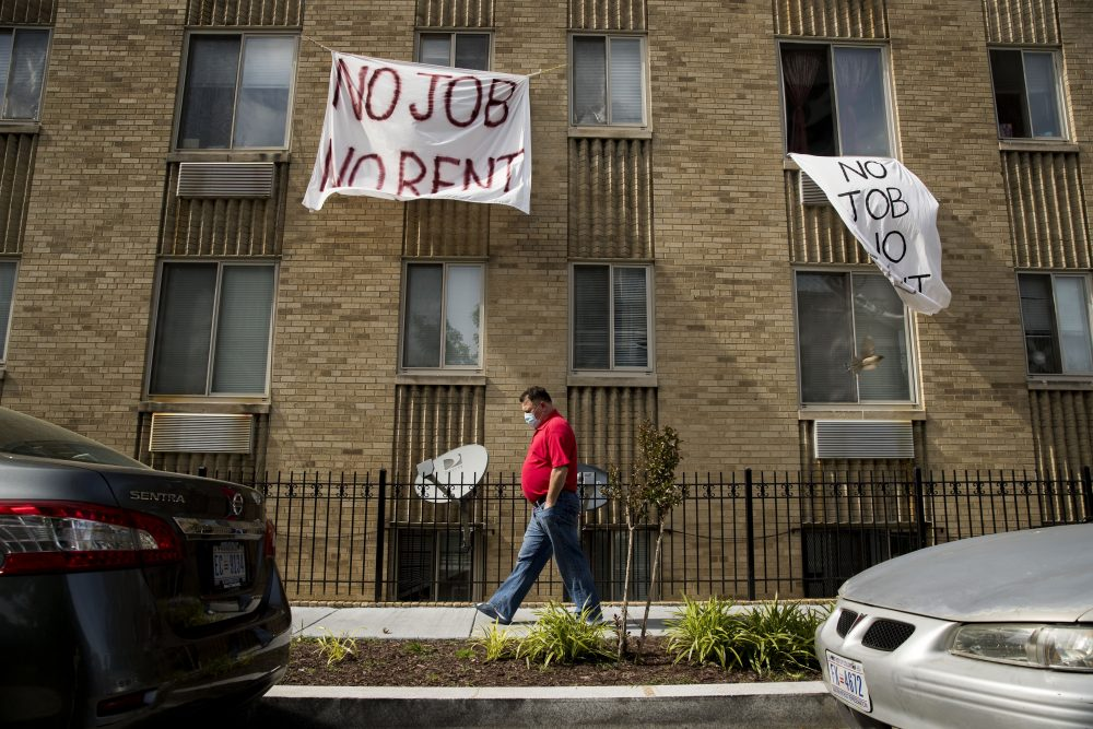 "Signs that read ""No Job No Rent"" hang from the windows of an apartment building in Washington. Once the federal moratorium ends on Friday, landlords can give their delinquent tenants 30 days' notice and then begin filing eviction paperwork in late August."