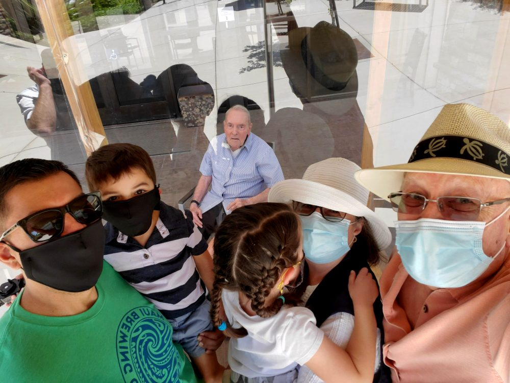 "Wake Sharp, 93, center behind plexiglass, visiting with three other generations of his family for Father's Day on Sunday in Fairfield, California. This setup, in which they talk by phone, has enabled the family to visit in person during the coronavirus pandemic. Sharp's son Dan Sharp, on the right, says, ""I don't know who enjoys it more. My family and I – or dad."" He paused then added, ""Probably dad."" Wake Sharp is a World War II veteran who worked for years as a vice president for the Montgomery Ward department store chain."