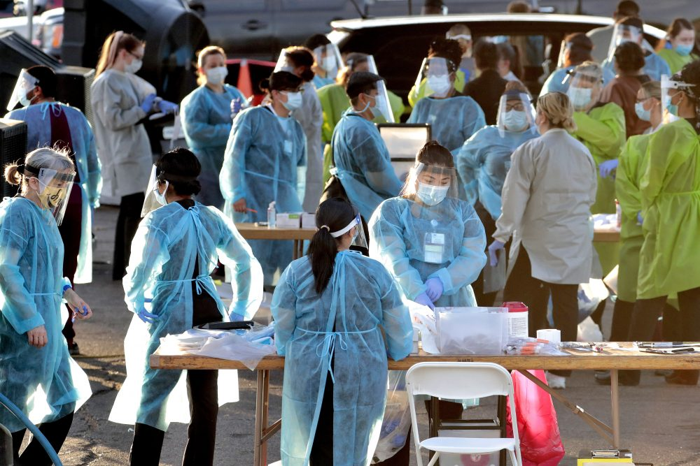 Medical personnel prepare to test hundreds of people lined up in vehicles in Phoenix's western neighborhood of Maryvale for COVID-19 tests on June 27. Hospitalizations rose to their highest levels to date in Arizona and Nevada as of Sunday.