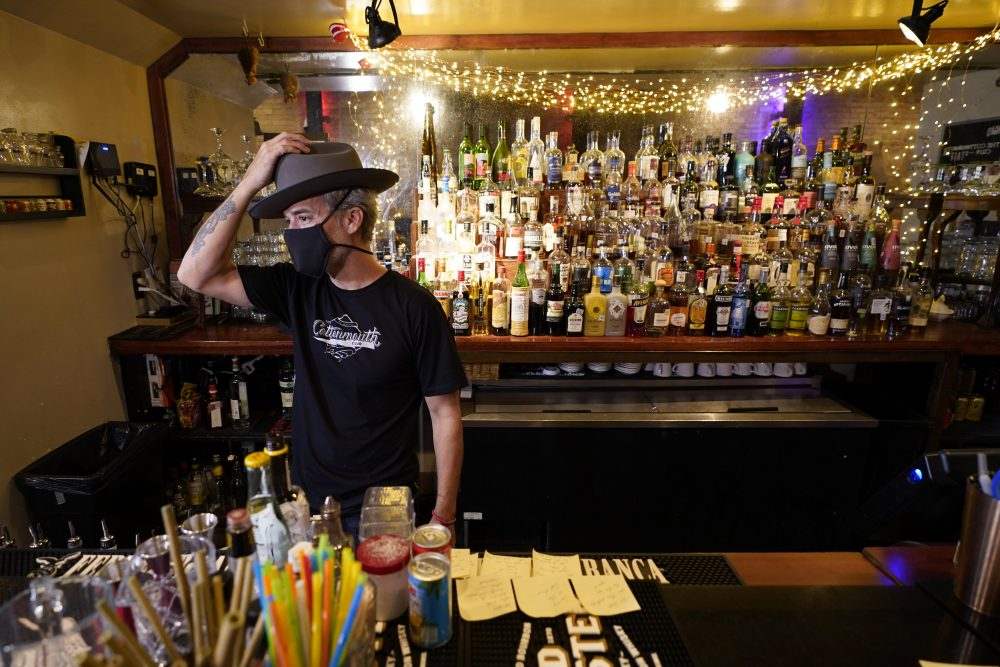 Michael Neff, co-owner of the Cottonmouth Club, adjusts his hat as he stands behind the bar Tuesday in Houston. Neff closed his downtown bar because of concerns within the industry as the number COVID-19 case continues to rise in Houston.