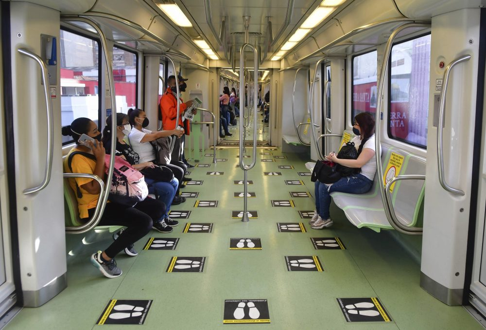 Commuters travel on a train marked with social distancing graphic cues, amid the new coronavirus pandemic, June 8 in Medellin, Colombia. The metropolis recently went five weeks without a single COVID-19 death.