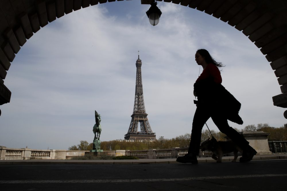 A woman walks her dog on a Paris bridge, with the Eiffel tower in background, in April during a nationwide confinement to counter the COVID-19. The European Union announced Tuesday that it will reopen its borders to travelers from 14 countries, but most Americans have been refused entry for at least another two weeks due to soaring coronavirus infections in the U.S.