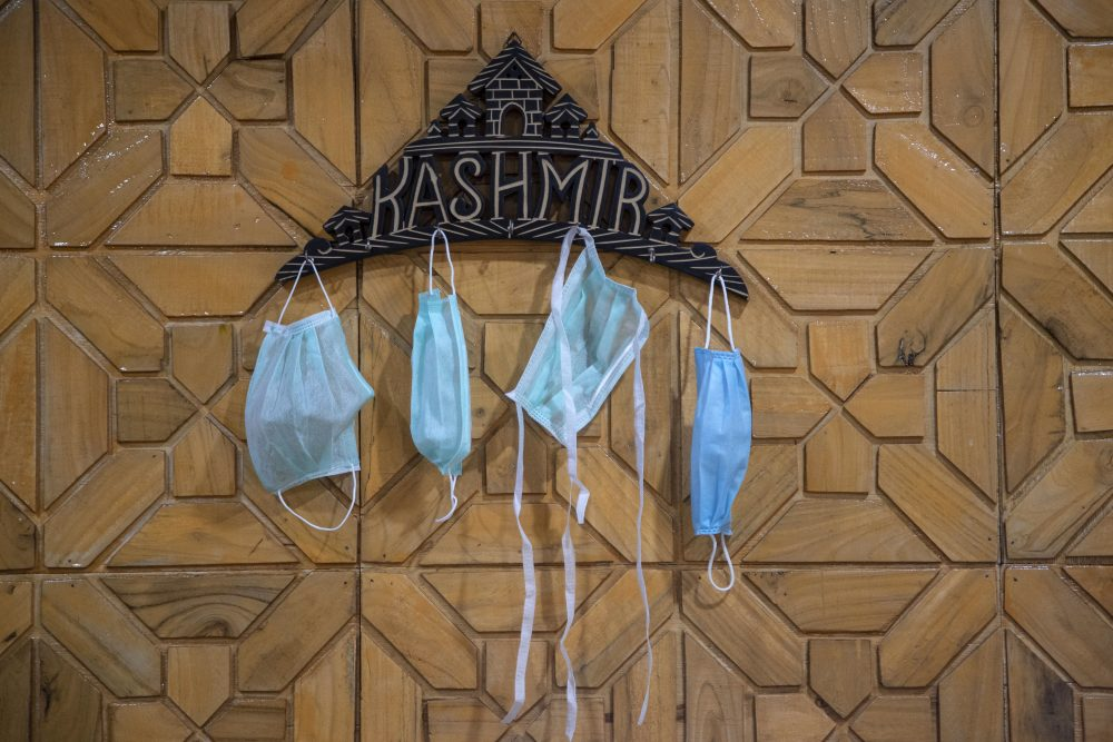 Surgical masks hang on a key holder inside a residential house Saturday in Srinagar, India.