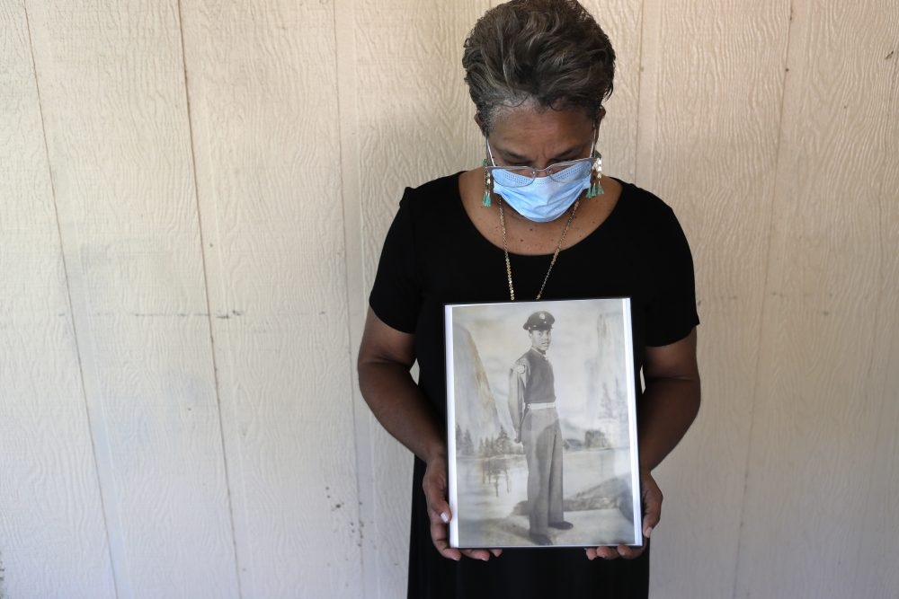 Belvin Jefferson White holds a portrait of her father, Saymon Jefferson, on May 18 at Saymon's home in Baton Rouge, La. Belvin recently lost both her father and her uncle, Willie Lee Jefferson, to COVID-19.