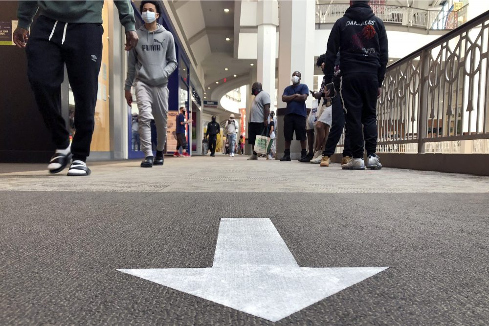 Shoppers walk near a social distancing arrow on a carpet in a hallway at Providence Place shopping mall in June in Providence, R.I. The mall has taken safety measures in response to the pandemic, including safe-distancing signage and hand-sanitizing stations in common areas.