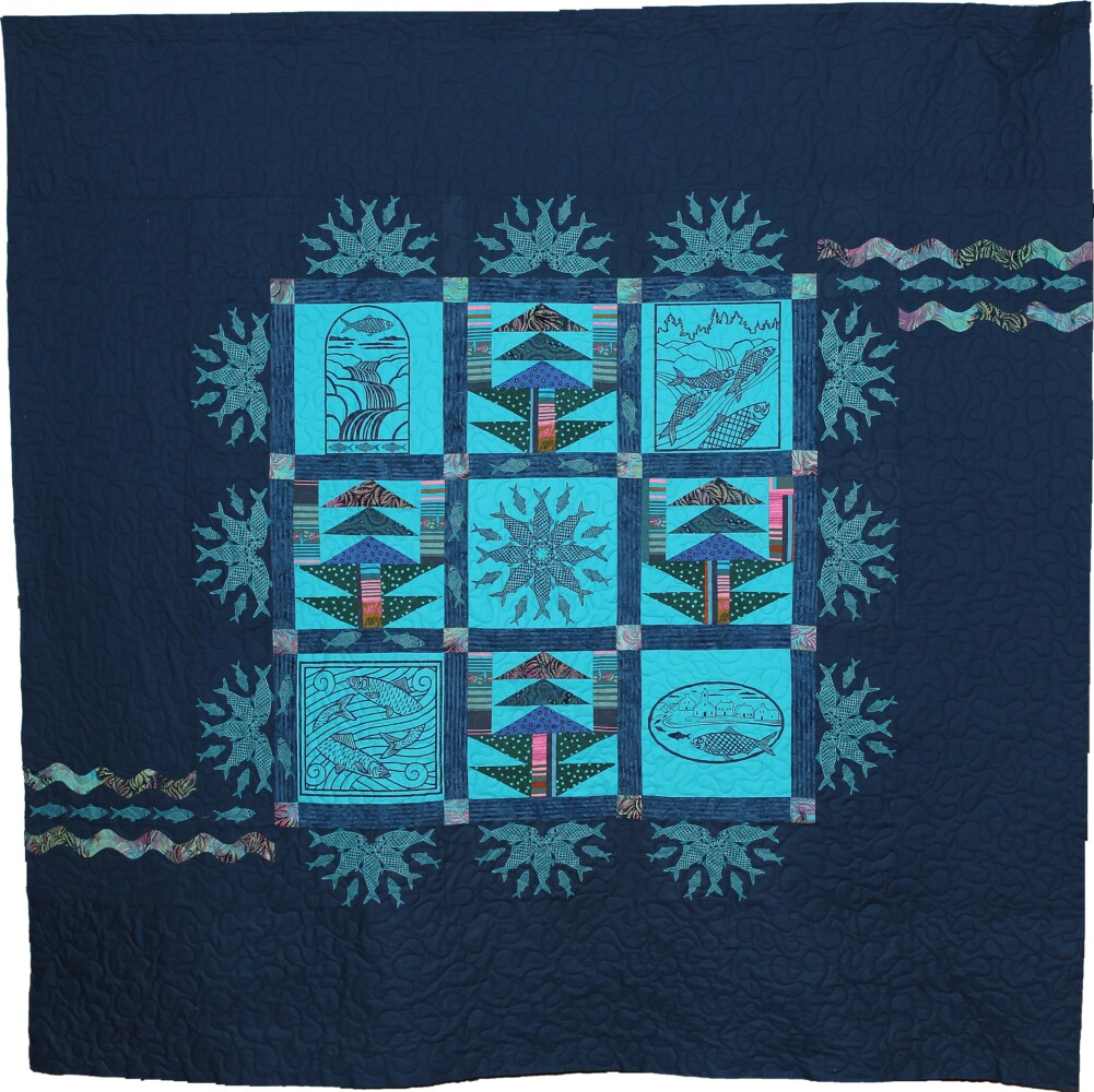 The Damariscotta Mills Alewife Festival Quilt was pieced by Betty Lu Brydges and machine quilted by Lynn Vogt. It includes silk screened designs drawn by local artists for festival goods and gear imprints in previous years.