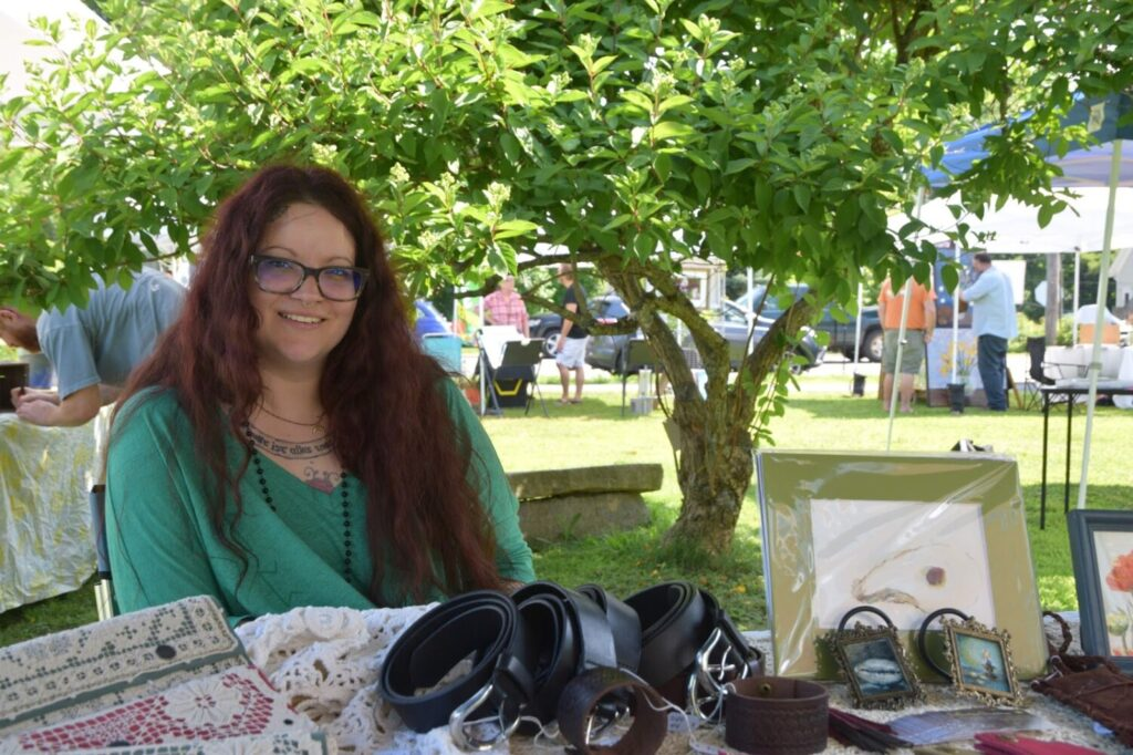 Katherine Devereux, here representing her business SPINNE Leather & Textiles, showcasing beautiful leather goods, oil and watercolor paintings, and home decor at the Belfast Farmers Market in 2019.