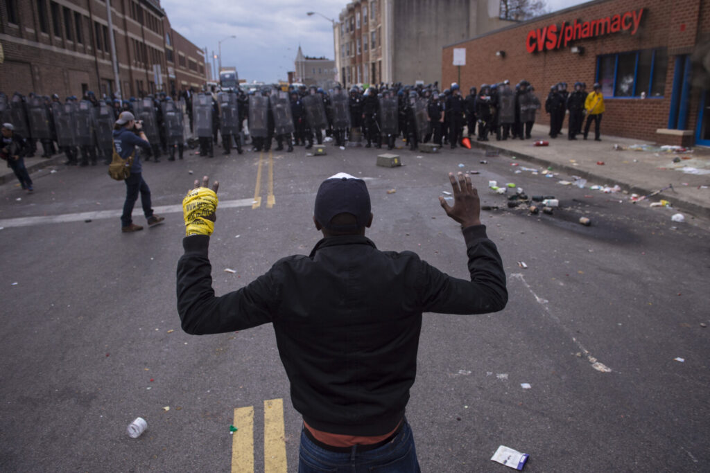 People stand with their hands up as officers move toward them during a protest for Freddie Gray in Baltimore on April 27, 2015.