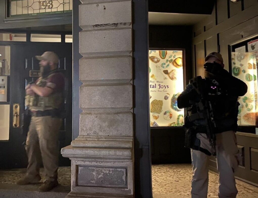 Two unidentified armed men stand guard outside an Old Port building during an anti-racism demonstration Tuesday.