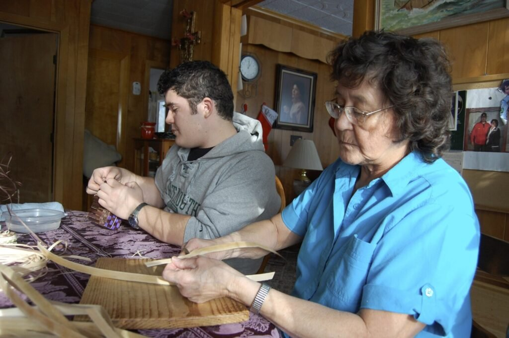 Molly Neptune Parker of Princeton makes a basket with her grandson Geo Neptune in this 2012 file photo. Neptune Parker, a winner of a National Heritage Fellowship from the National Endowment for the Arts, has died.