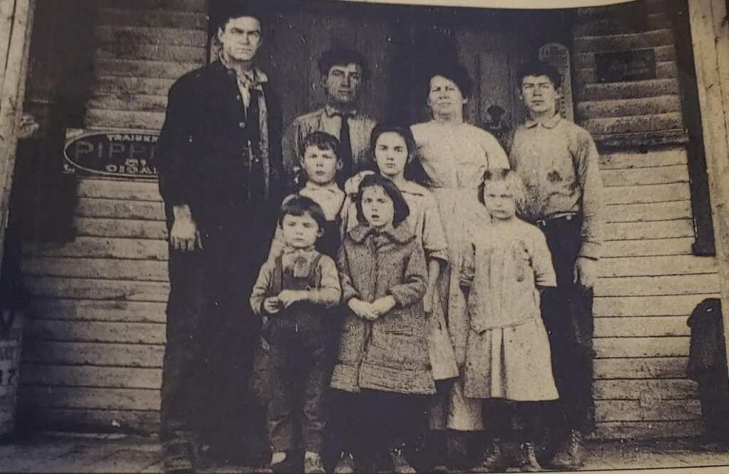 "Rosalie Colby's grandmother Grace Lockin is the oldest girl in the center of this family portrait taken in front of the grocery store her father ran out of their home in Brownfield, circa 1914. The Maine Sunday Telegram wrote about Grace Lockin in 1933, and  her recipe for potato fudge appears in the ""Maine Bicentennial Cookbook."""