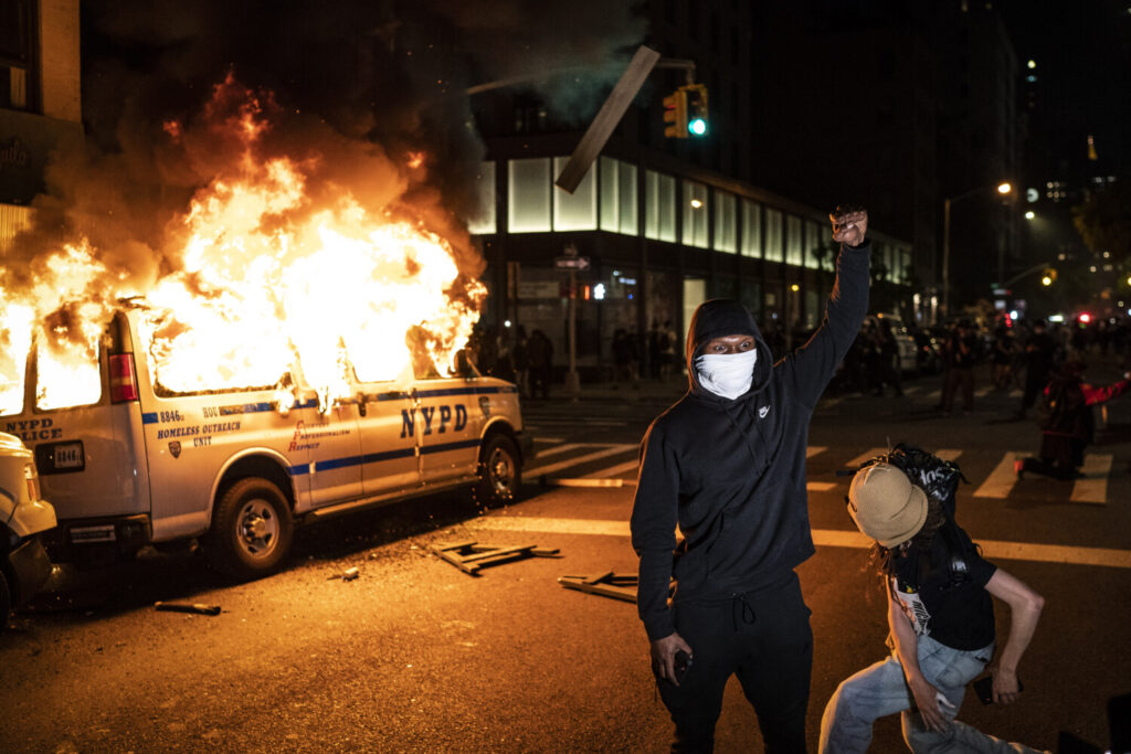 A police vehicle burns during protests Saturday in New York City, where some officers say they have been attacked and targeted by drivers.