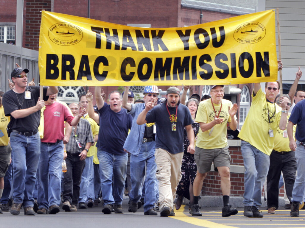 Workers from the Portsmouth Naval Shipyard walk through gate 1 cheering the BRAC Commission's decision to keep the shipyard open in August 2005.