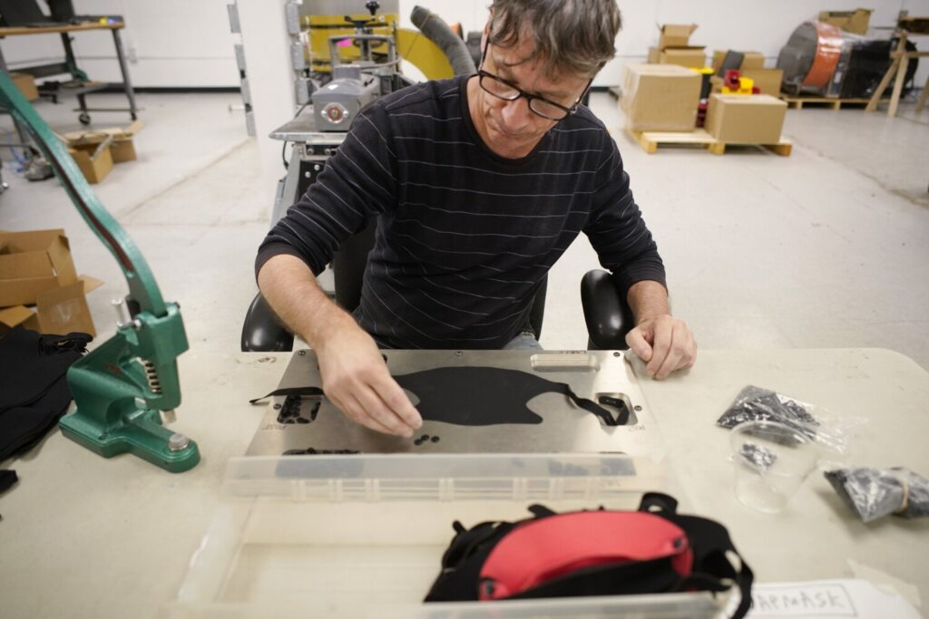 John Bemis gathers snap parts Tuesday while demonstrating how to assemble one of the masks that the Portland company Zootility is making. The company, known for its popular Careful Key, started designing masks in March and sells them through its website and at retail outlets in Portland.